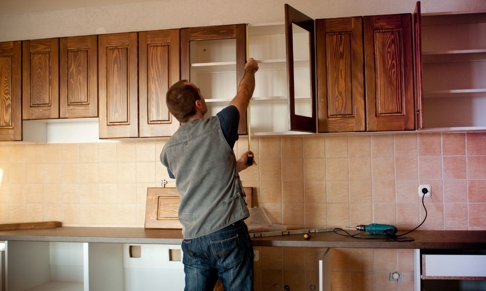 Image of man measuring height of cabinets in kitchen.